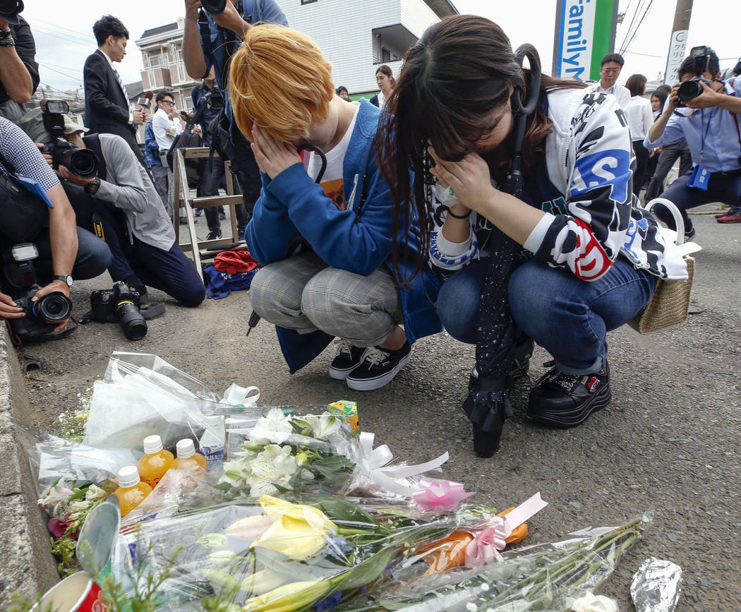 Women pray after offering flowers near the scene where a man wielding a knife attacked commuter ...