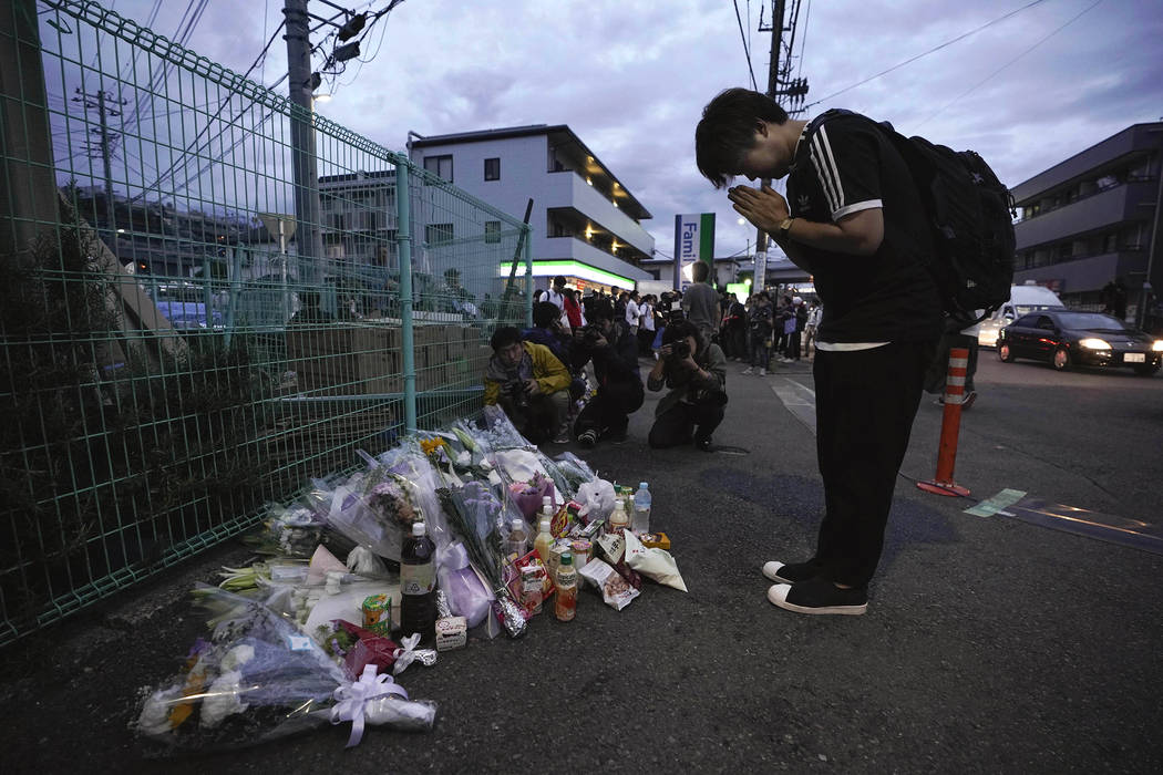 A man pays respects at a makeshift memorial for the victims of a knife attack Tuesday, May 28, ...
