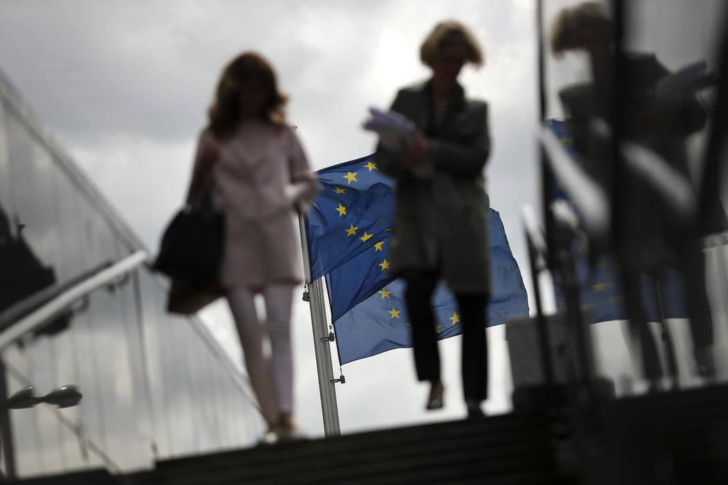 Two women walk near EU flags outside the European Commission headquarters in Brussels, Monday, ...