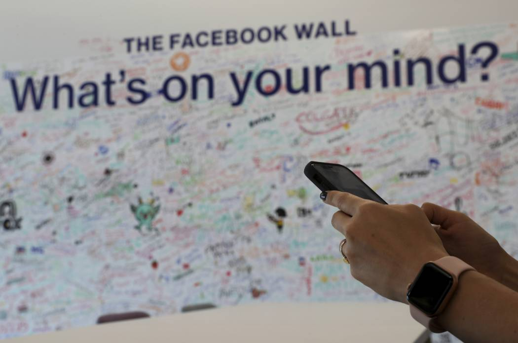 In this Monday, May 20, 2019 photo, a woman uses her mobile at the Facebook office in Dubai, Un ...