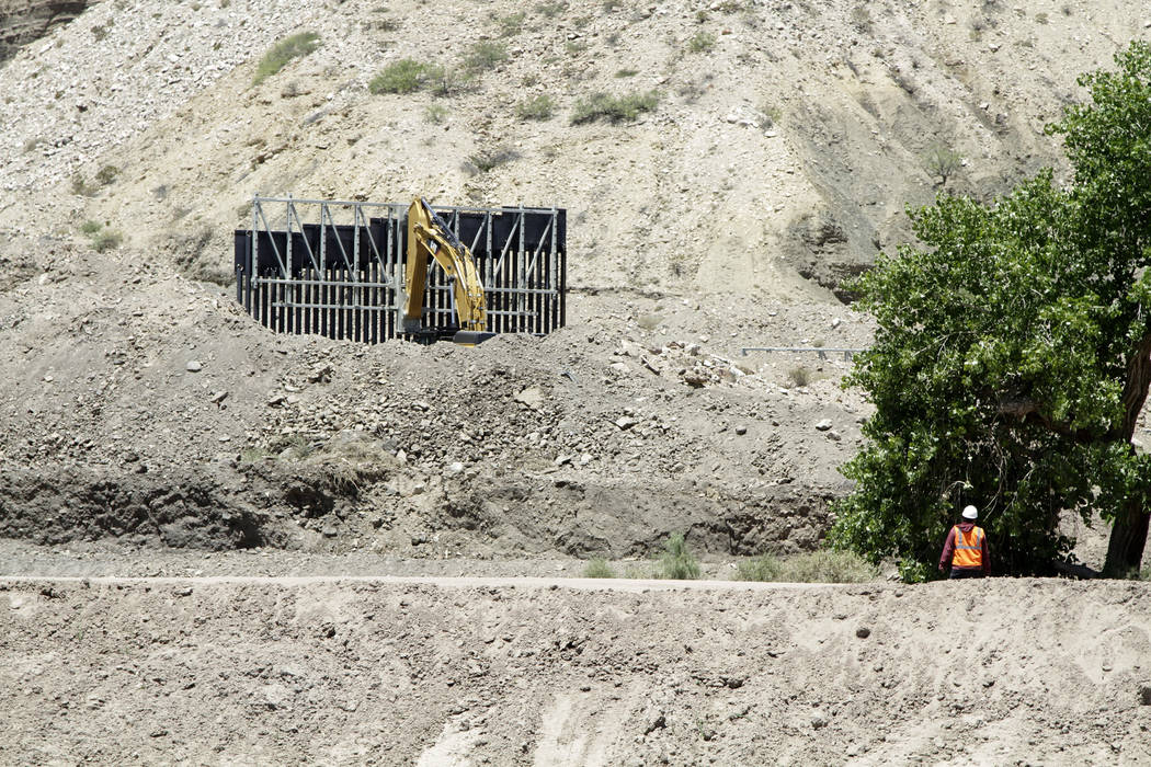 In a May 24, 2019 photo, a construction worker watches a section of fencing be moved for a priv ...