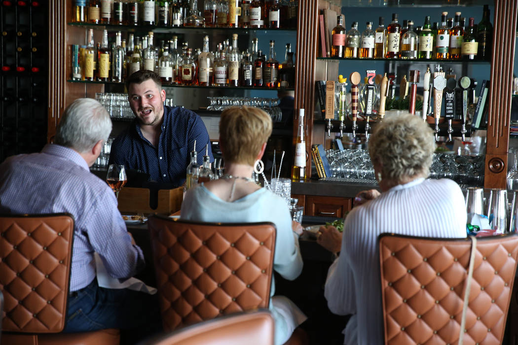 Bartender Liam Grosshauser speaks to customers at the Kitchen at Atomic in Las Vegas, Friday, M ...