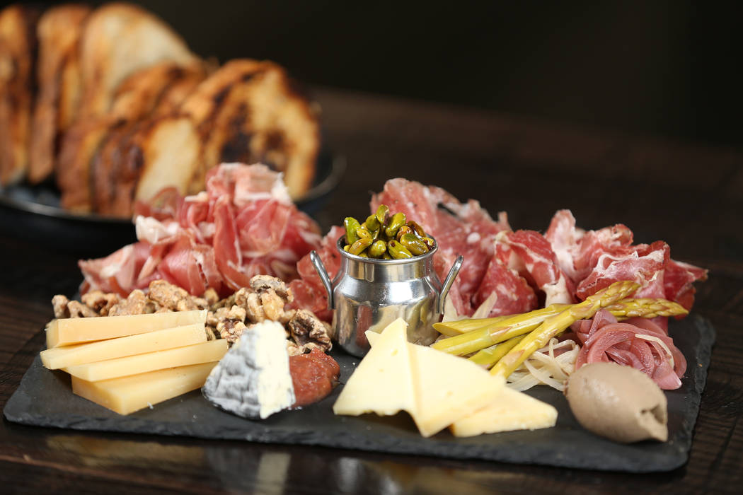 The harvest board is served with cheese, charcuterie, fruit preserves, candied nuts, pickles, a ...