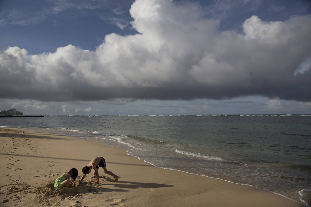 FILE - In this Aug. 25, 2015, file photo two children visiting from China play on Waikiki Beach ...