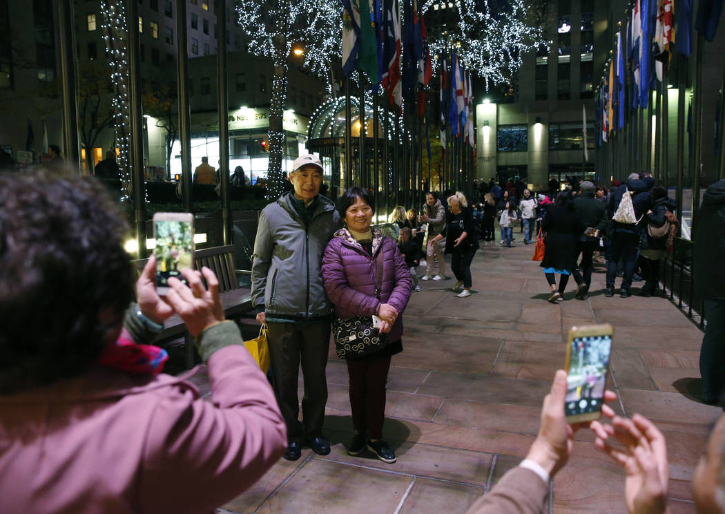 FILE - In this Nov. 12, 2017, file photo tourists from China pose for photographs at Rockefelle ...