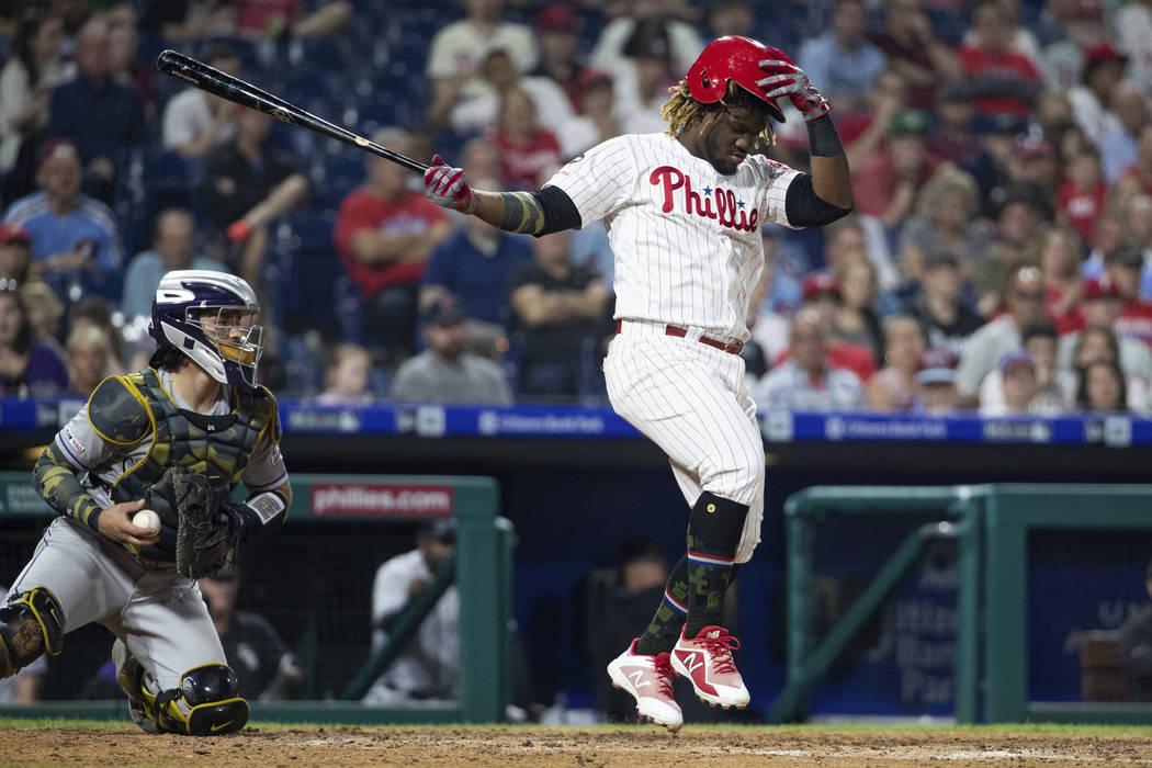 Philadelphia Phillies' Odubel Herrera holds onto his helmet on the swing during the sixth innin ...