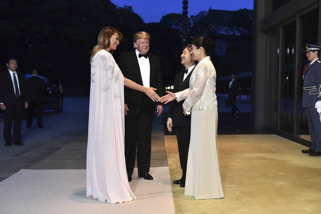 U.S. President Donald Trump, center left, and First lady Melania Trump, front left, are greeted ...