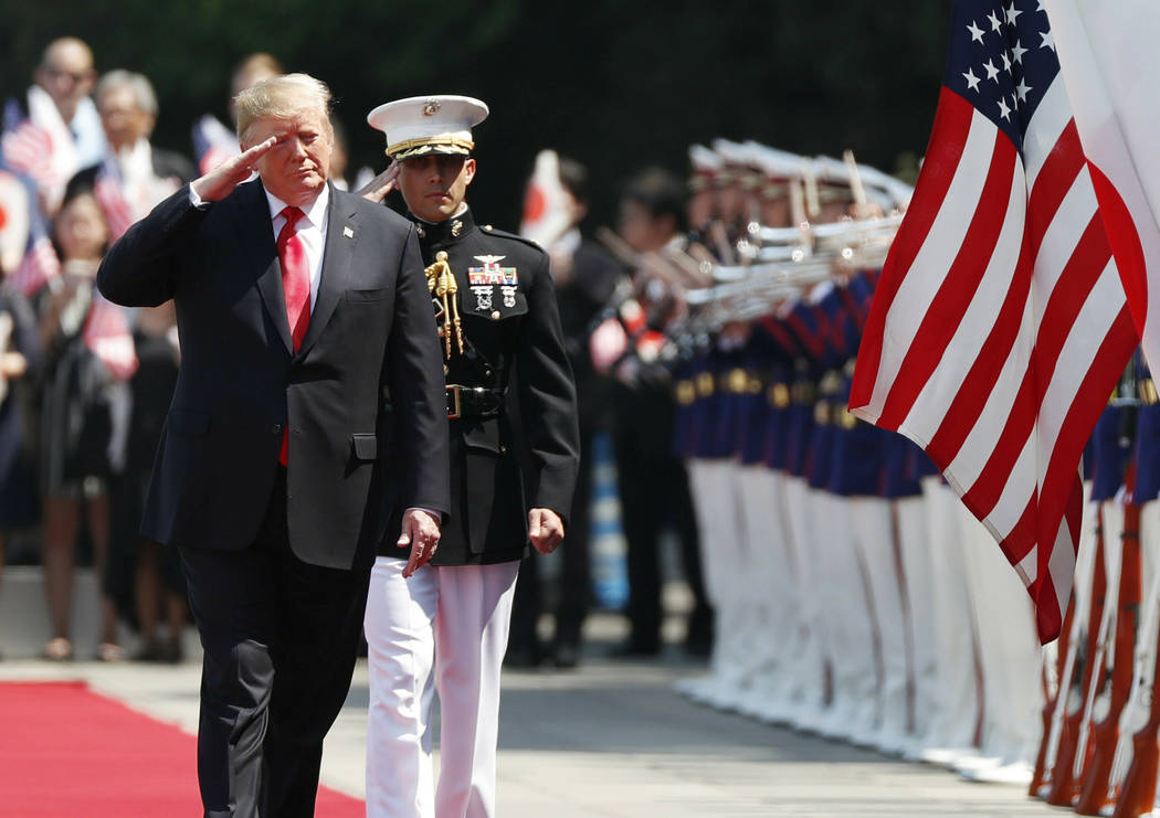 U.S. President Donald Trump, left, reviews an honor guard during a welcome ceremony at the Impe ...