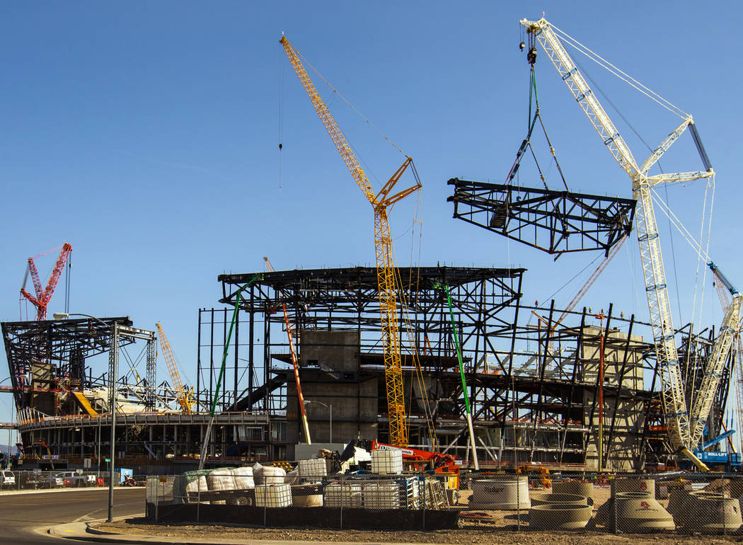 The newest truss is slowly lowered and attached into place at the top of Raiders Las Vegas Stad ...