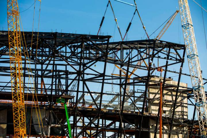 The newest truss is lowered into place and attached by awaiting steelworkers at the top of Raid ...