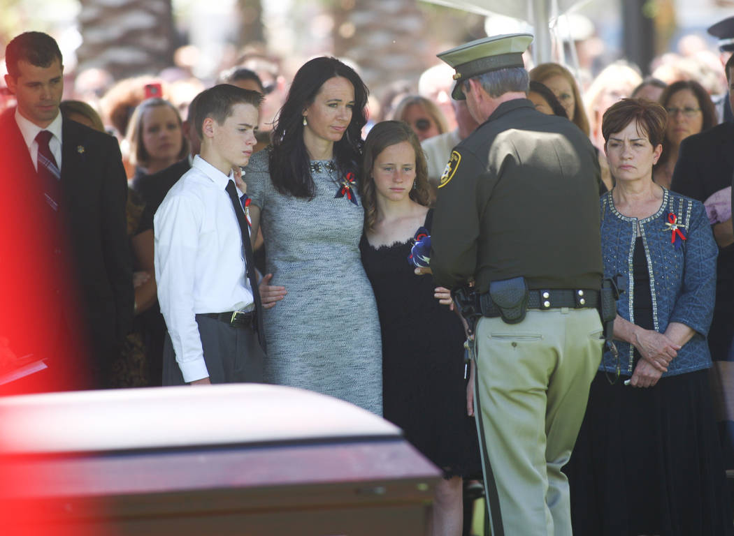 Sheriff Doug Gillespie, right, presents a flag to the family of fallen Las Vegas police officer ...