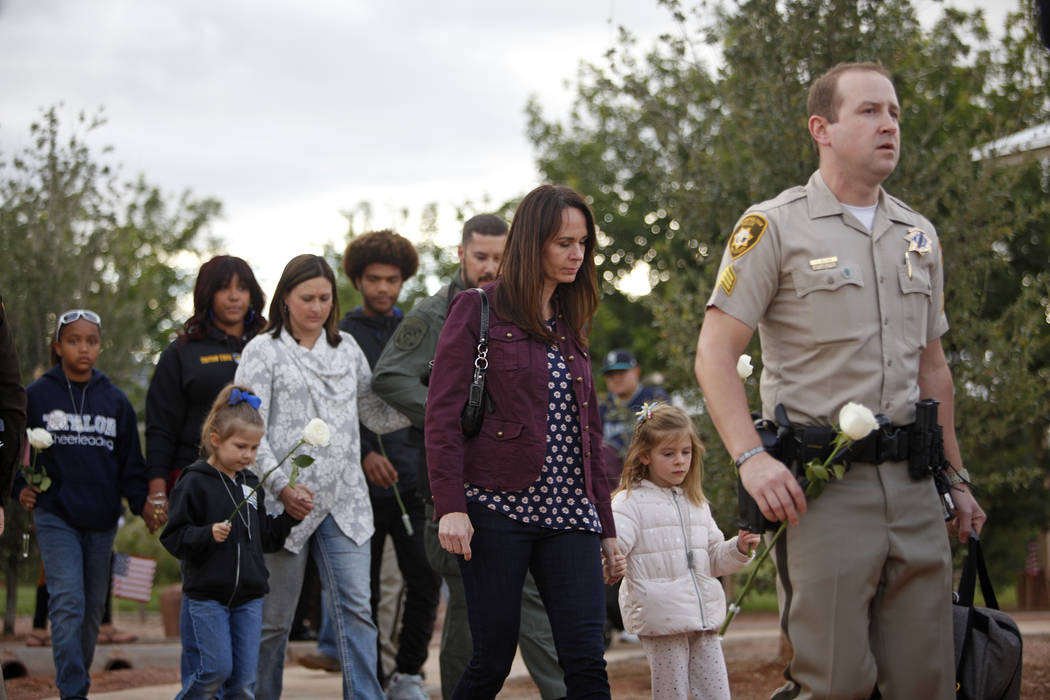 Nicole Beck, the widow of Las Vegas police officer Alyn Beck, walks with her daughter Katriann, ...