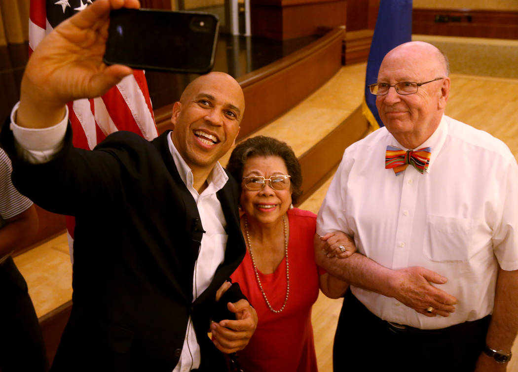 Presidential hopeful Sen. Cory Booker, D-N.J., takes a selfie with Cristina and Ed Drost of Hen ...