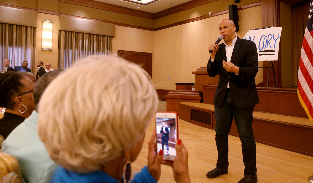 China Frazier of Henderson takes a photo of presidential hopeful Sen. Cory Booker, D-N.J., spea ...