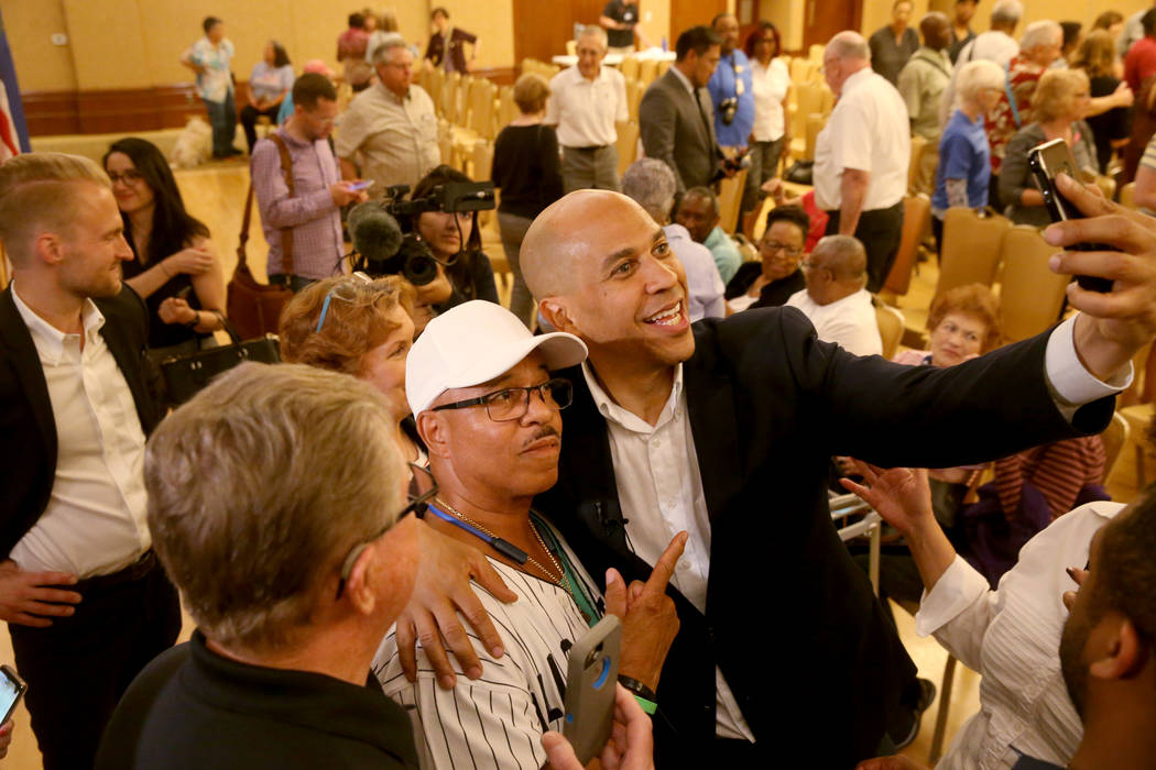 Presidential hopeful Sen. Cory Booker, D-N.J., takes a selfie with Jonathan Collins of Henderso ...