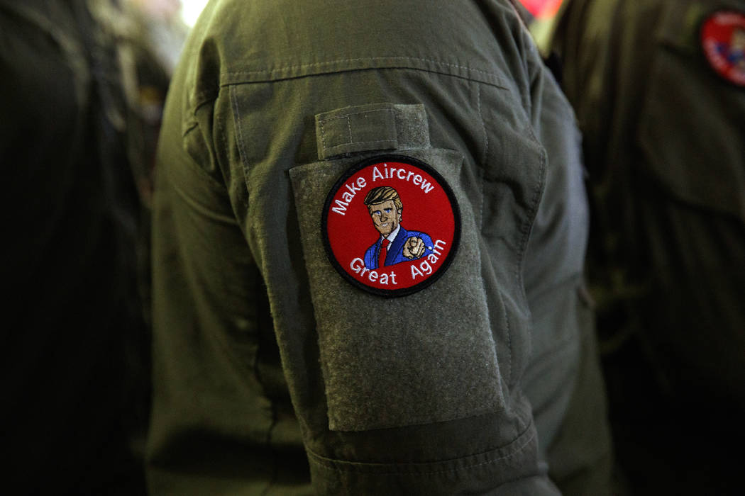 "A service member wears a patch that says ""Make Aircrew Great Again"" as they listen to ..."
