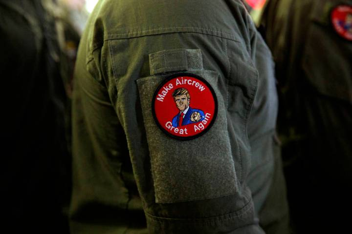 """A service member wears a patch that says """"Make Aircrew Great Again"""" as they listen to ..."""