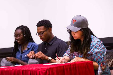 Savannah Mantanona, of Basic High School, right, signs paperwork during a ceremony for high sch ...