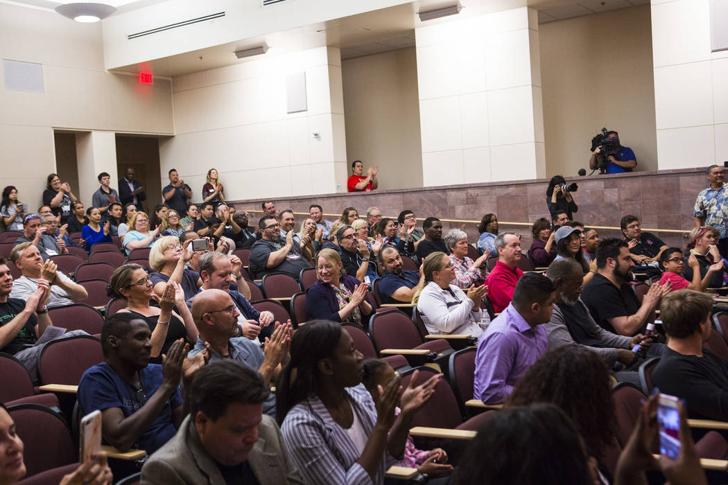 Attendees cheer during a signing ceremony for recent high school graduates that were hired by T ...