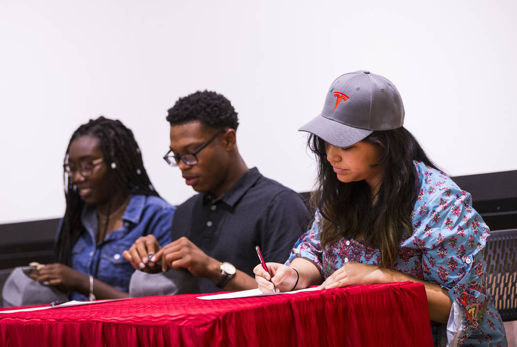Savannah Mantanona, of Basic High School, right, signs paperwork during a signing ceremony for ...