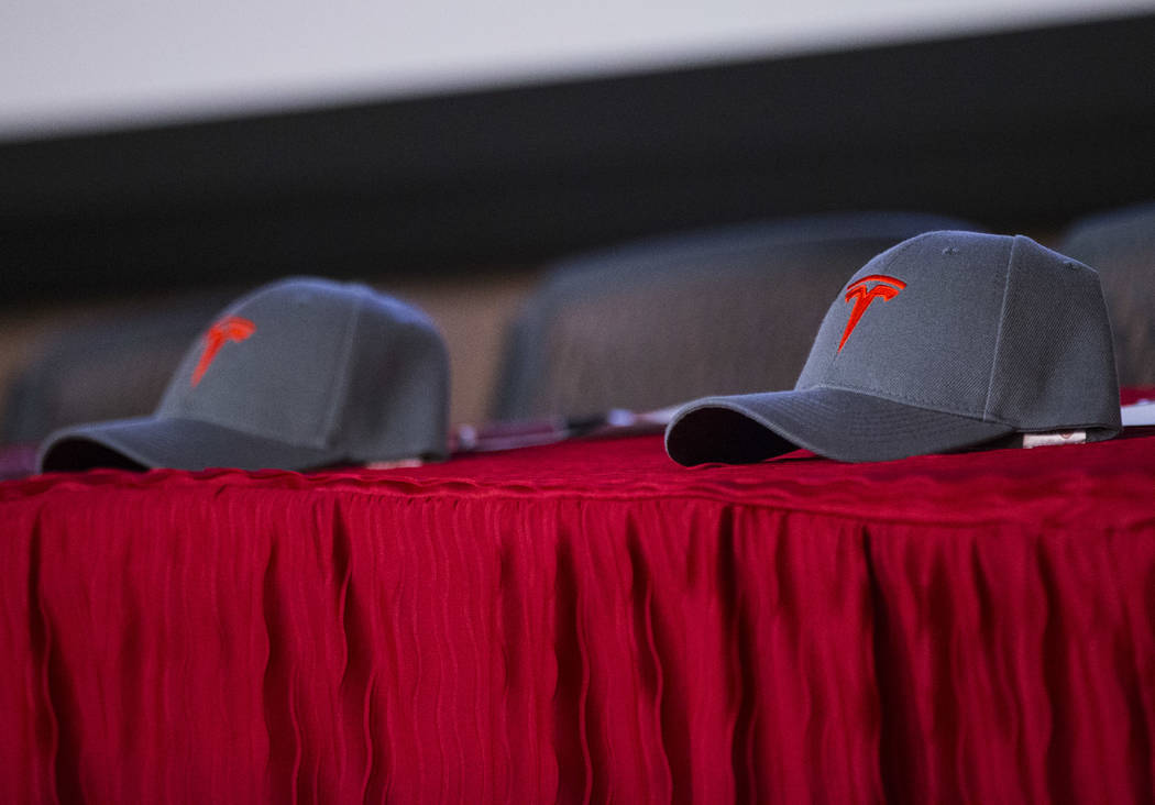 Tesla hats sit on a table at the start of a signing ceremony for recent high school graduates t ...