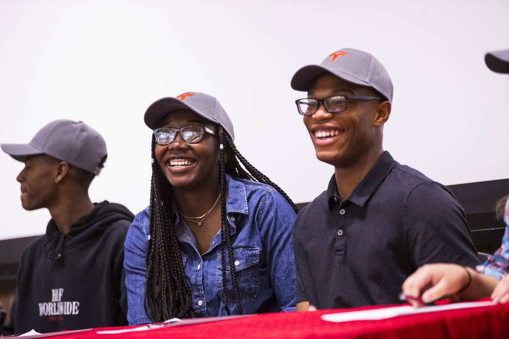 Centennial graduates DeRajanique McKinney, center left, and Jayquan Jackson, right, react durin ...