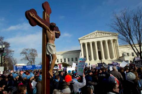 In this Friday, Jan. 18, 2019 file photo, anti-abortion activists march outside the U.S. Suprem ...