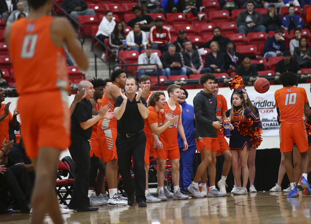 Bishop Gorman head coach Grant Rice, center left in black, celebrates as his team leads against ...