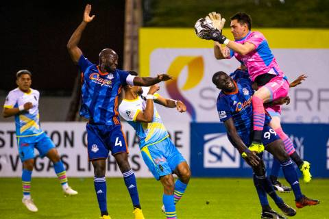 (From right) Las Vegas Lights FC goalkeeper Thomas Olsen (1) grabs a shot on goal over Tulsa Ro ...