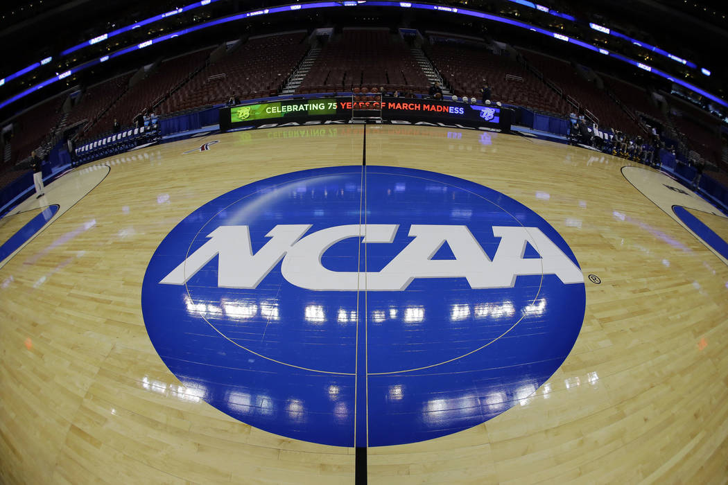 In this March 21, 2013, file photo, taken with a fisheye lens, the NCAA logo is displayed on th ...