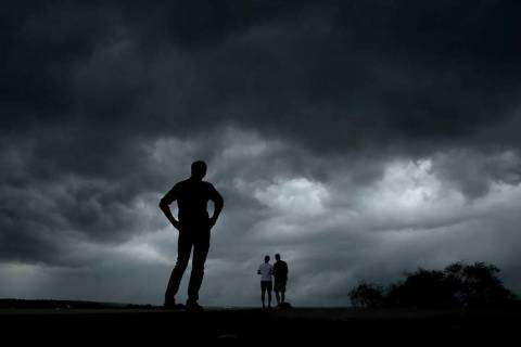 People watch from the Liberty Memorial as a severe storm that dropped several tornados earlier ...