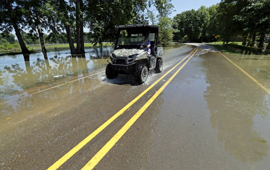 In this Thursday, May 23, 2019 photo, a Holly Bluff, Miss., resident drives through backwater f ...