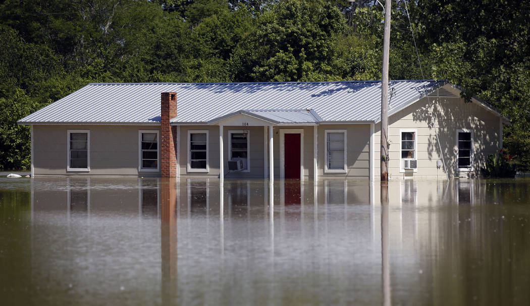 In this Thursday, May 23, 2019 photo, floodwaters overtake a home in Holly Bluff, Miss. It&#x20 ...