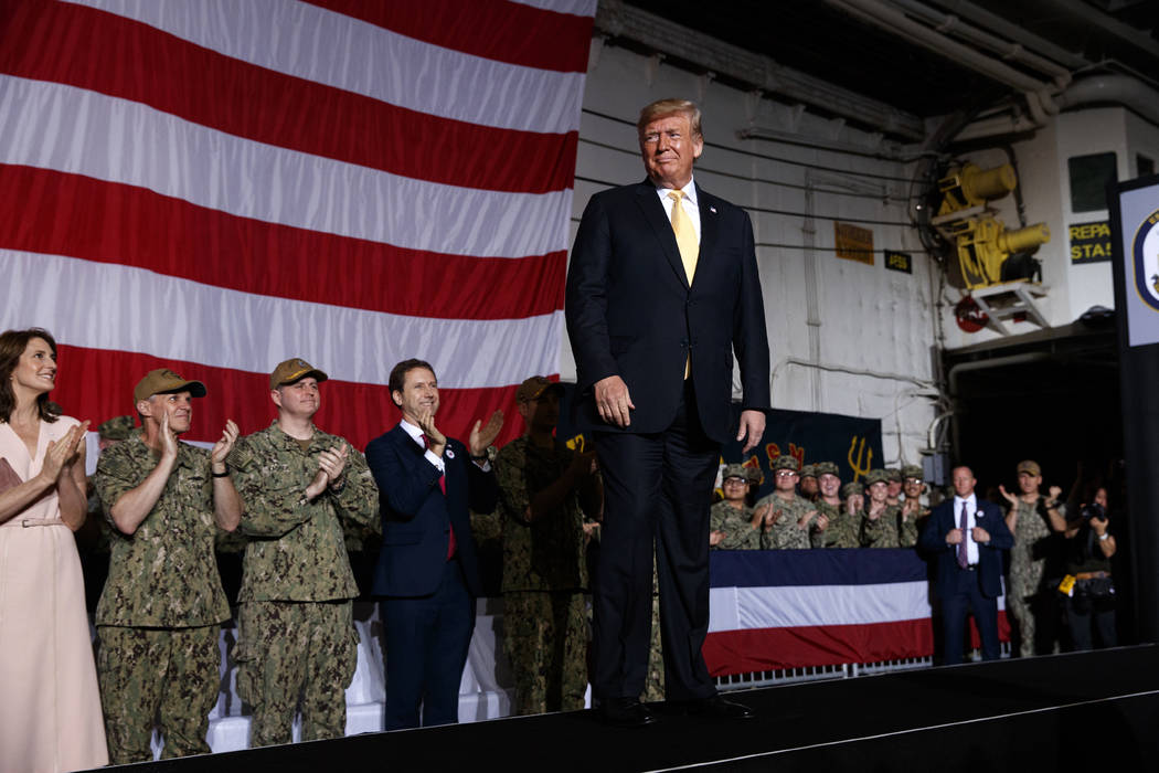 President Donald Trump arrives on stage to speak to troops at a Memorial Day event aboard the U ...
