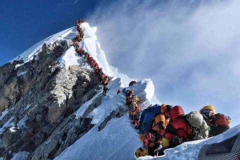 In a May 22, 2019 photo, a long queue of mountain climbers line a path on Mount Everest. About ...