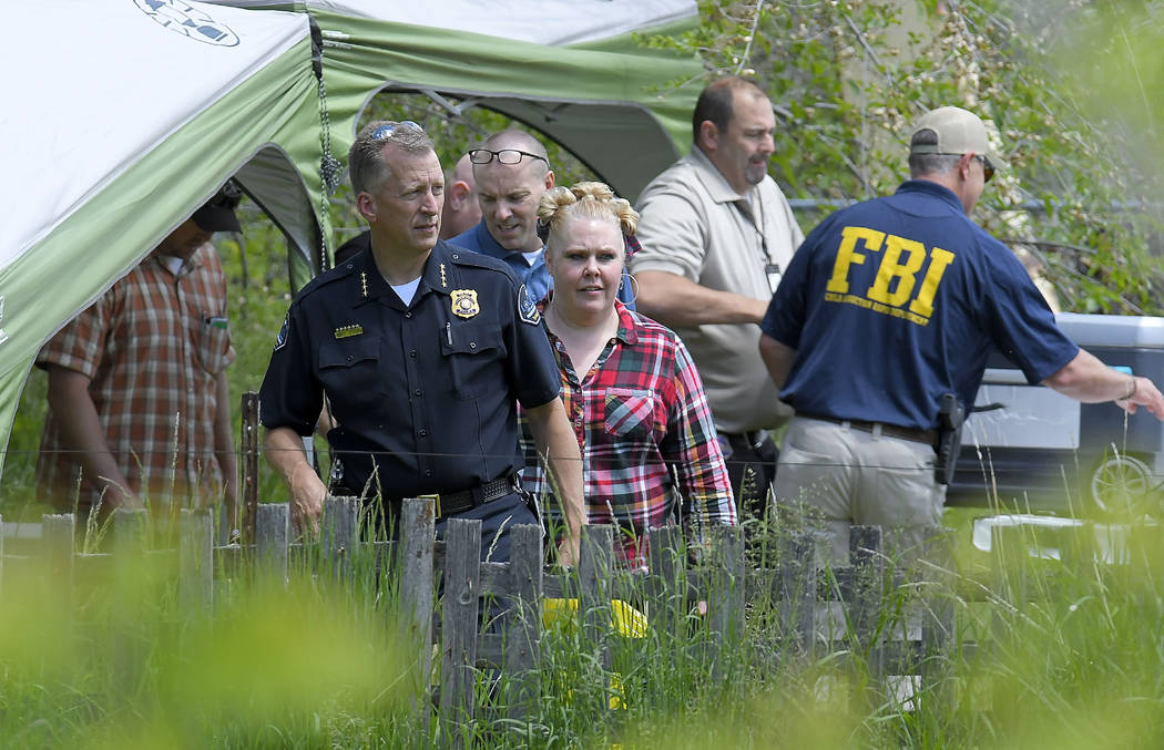 Law enforcement investigate the scene where a body that they believe to be Elizabeth Shelley wa ...