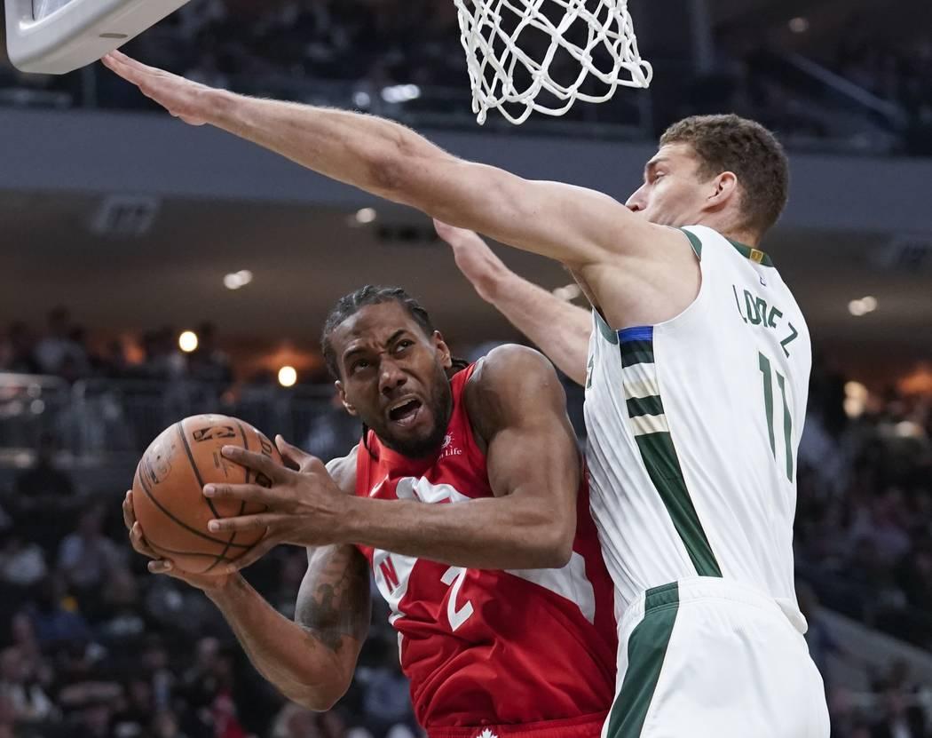 Toronto Raptors' Kawhi Leonard shoots past Milwaukee Bucks' Brook Lopez during the second half ...
