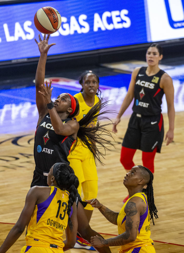 Las Vegas Aces guard Jackie Young (0) lays up the ball past Los Angeles Sparks forward/center C ...