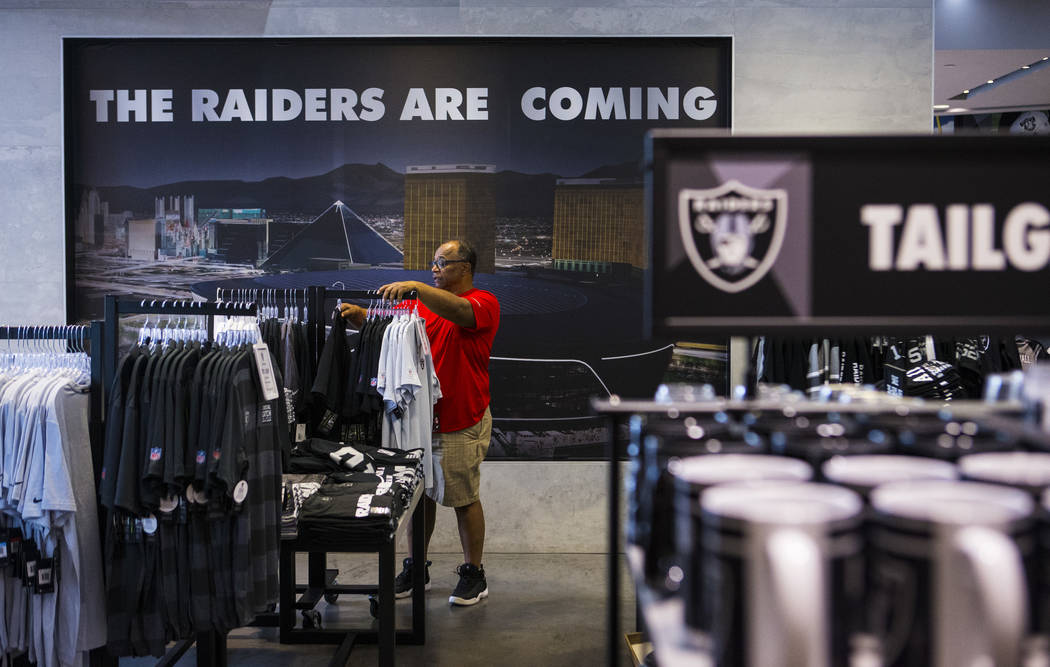 BJ Freeman, of Texas, looks through shirts and jerseys at The Raider Image store at the Galleri ...