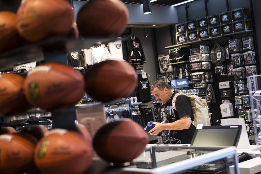 Nickolaus Gerencser, of Baldwin Park, Calif., buys items at The Raider Image store at the Galle ...