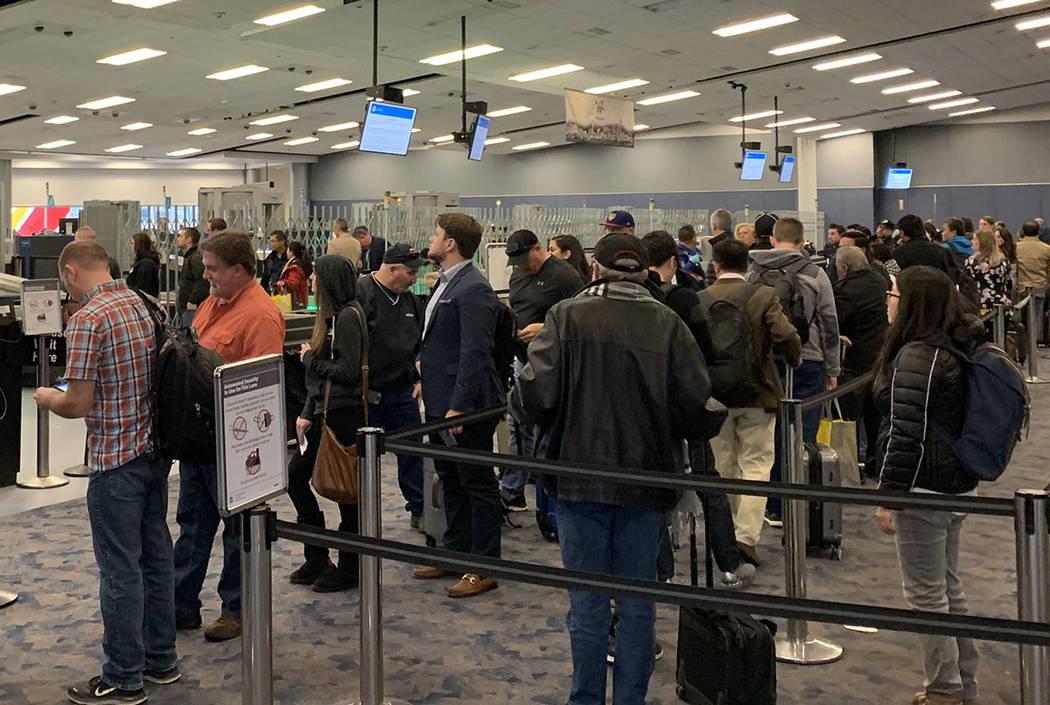 Passengers wait in the TSA screening line at McCarran International Airport in Las Vegas. (Mick ...