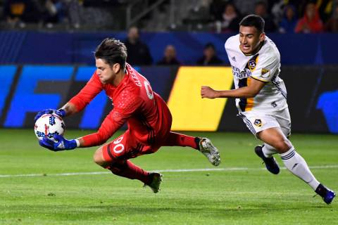 Portland Timbers goalkeeper Jake Gleeson, left, stops a shot as LA Galaxy forward Jose Villarre ...
