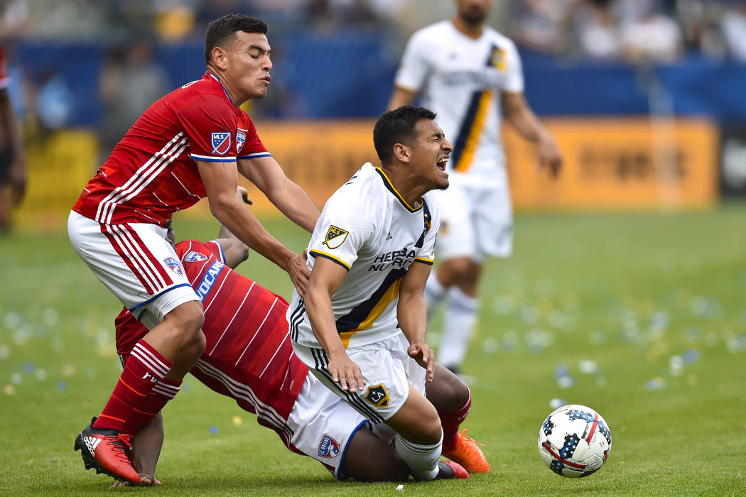 Los Angeles Galaxy midfielder Jose Villarreal, right, reacts as he gets tripped up by FC Dallas ...
