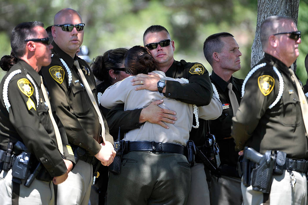 Las Vegas police officers console each during a service for officer Igor Soldo at Palm Northwes ...