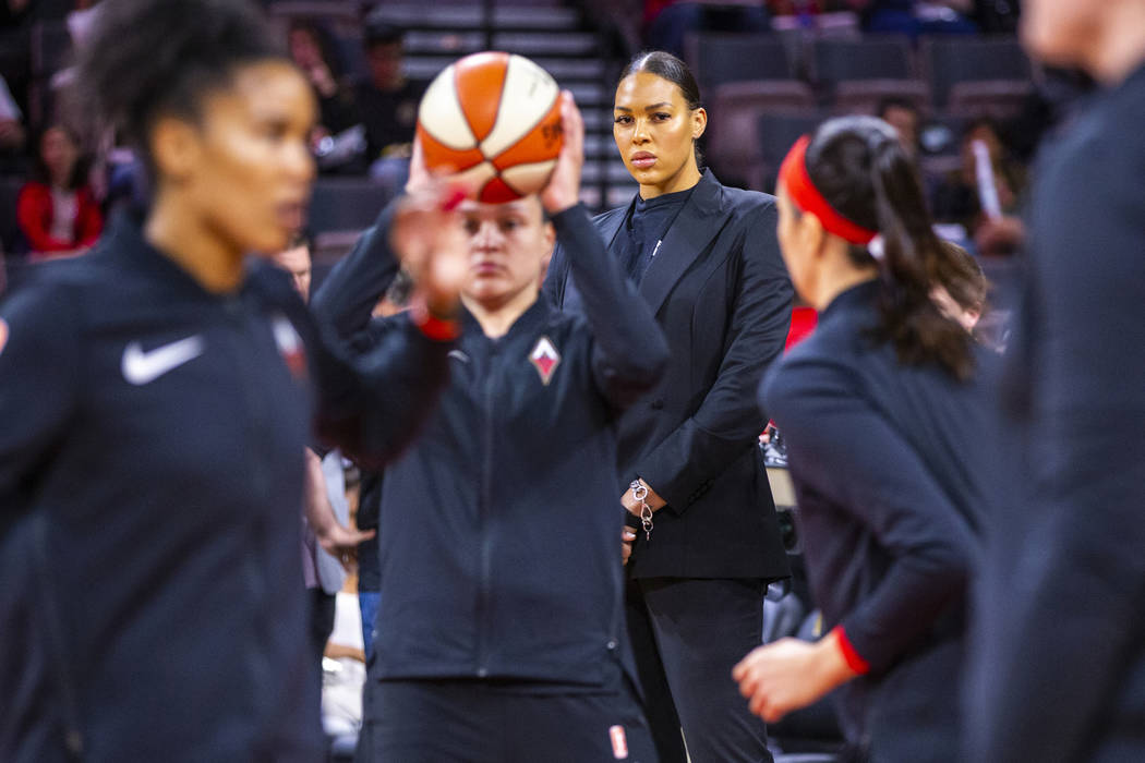 Las Vegas Aces center Liz Cambage (wearing street clothes) watches her teammates warm up before ...