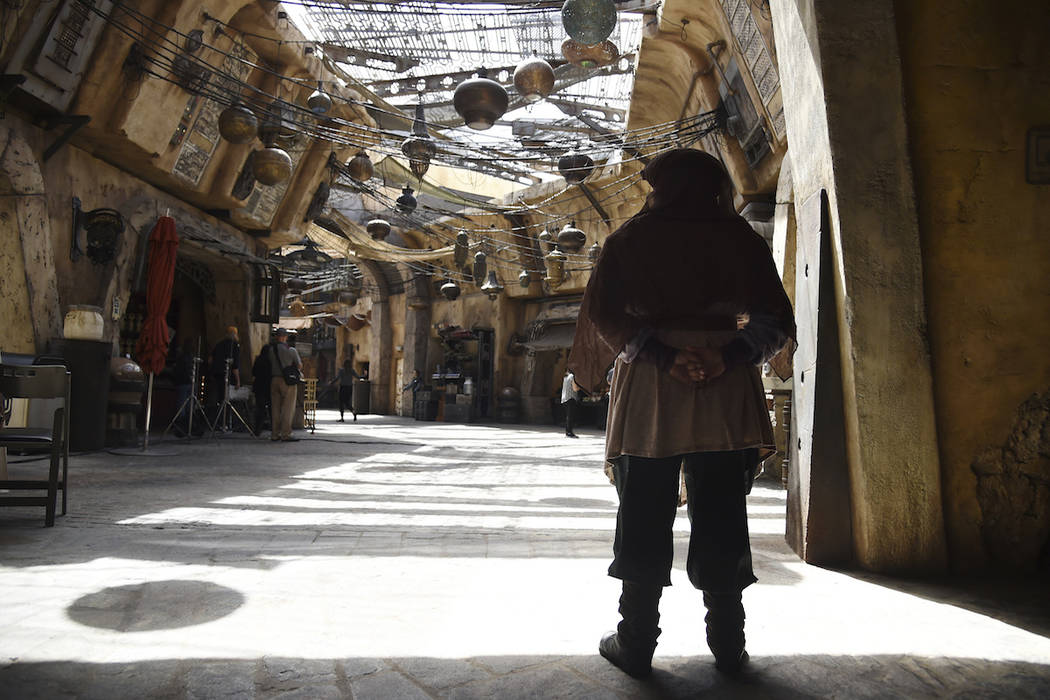 A character looks out to the marketplace in the Black Spire Outpost during the Star Wars: Galax ...