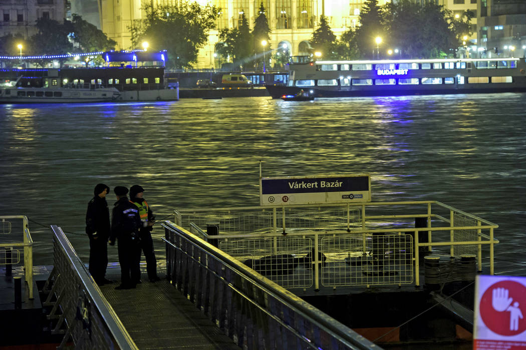 Police officers stand on a landing dock early Thursday, May 30, 2019 after a tourist boat crash ...