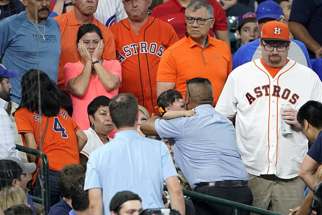A young child is carried from the stands after being injured by a foul ball off the bat of Chic ...
