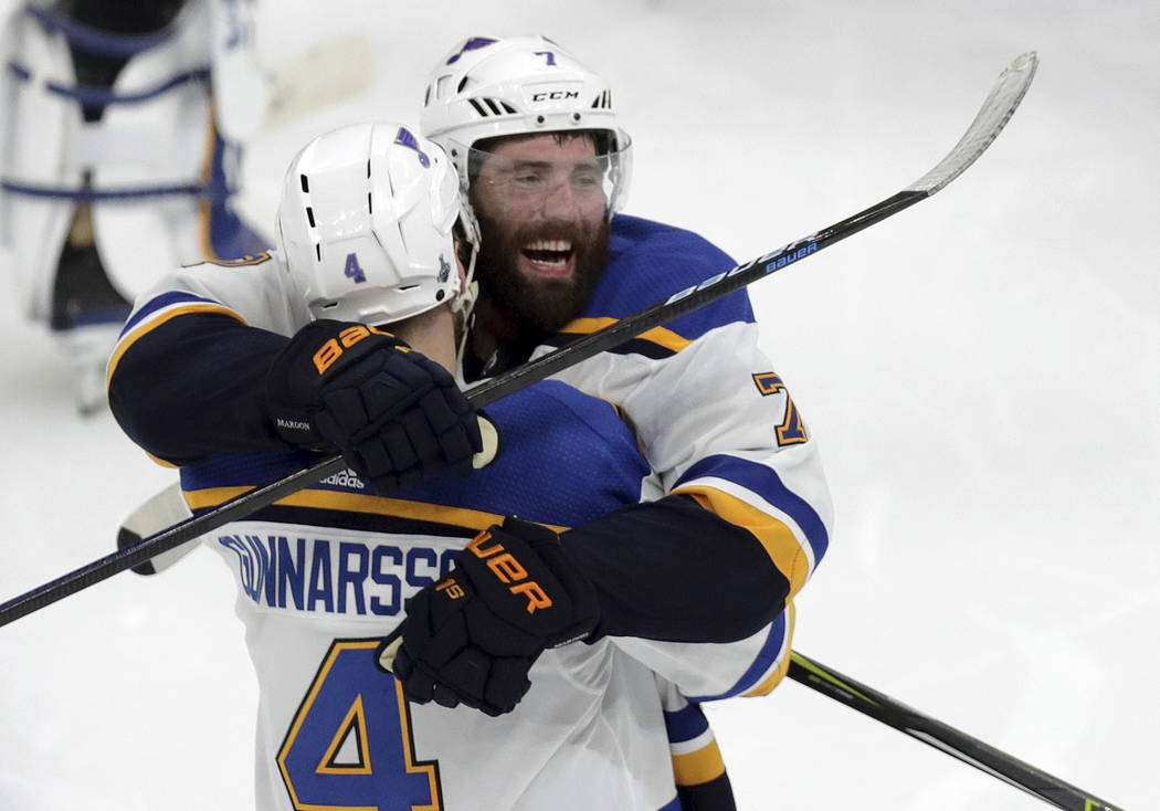 St. Louis Blues' Carl Gunnarsson (4), of Sweden, is congratulated by Pat Maroon, rear, after he ...