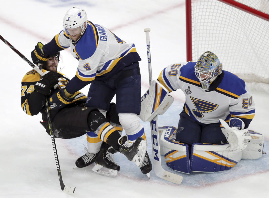 St. Louis Blues' Carl Gunnarsson (4), of Sweden, checks Boston Bruins' Jake DeBrusk (74) to the ...